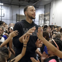 Golden State Warrior Stephen Curry greets basketball camp participants. A letter from a 9-year-old girl has helped Stephen Curry and Under Armour fix online access to his shoes for girls. (Jeff Chiu/AP)