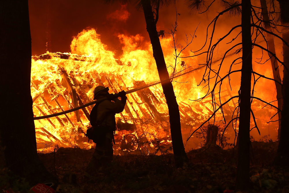 A Cal Fire firefighter sprays water on a home next to a burning home as the Camp Fire moves through the area on Nov. 9, 2018 in Magalia, Calif. (Justin Sullivan/Getty Images)