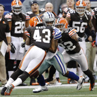 Cleveland Browns safety T.J. Ward hits Dallas Cowboys wide receiver Kevin Ogletree as Browns cornerback Buster Skrine helps tackle during the second half of an NFL football game in 2012. (AP/Brandon Wade, File)