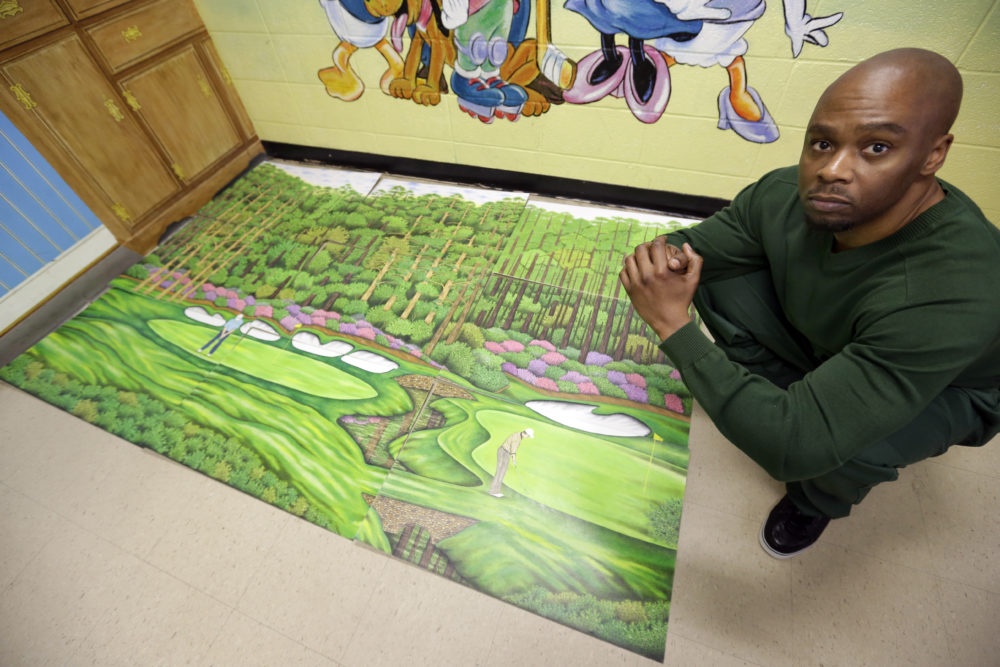 Valentino Dixon poses in 2013 with golf art he created while serving time for a murder he didn't commit. (David Duprey/AP)