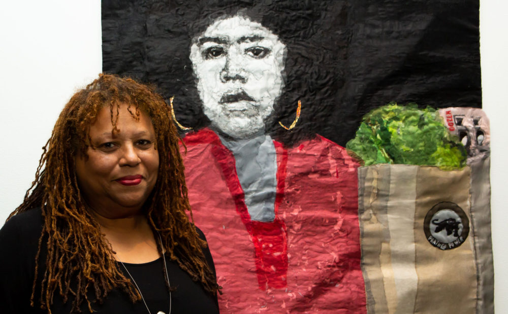 L'Merchie Frazier with her mixed media quilt which depicts Black Panther Party activist Ericka Huckins (Courtesy Melissa Blackall and Cooper Gallery of African and African American Art)
