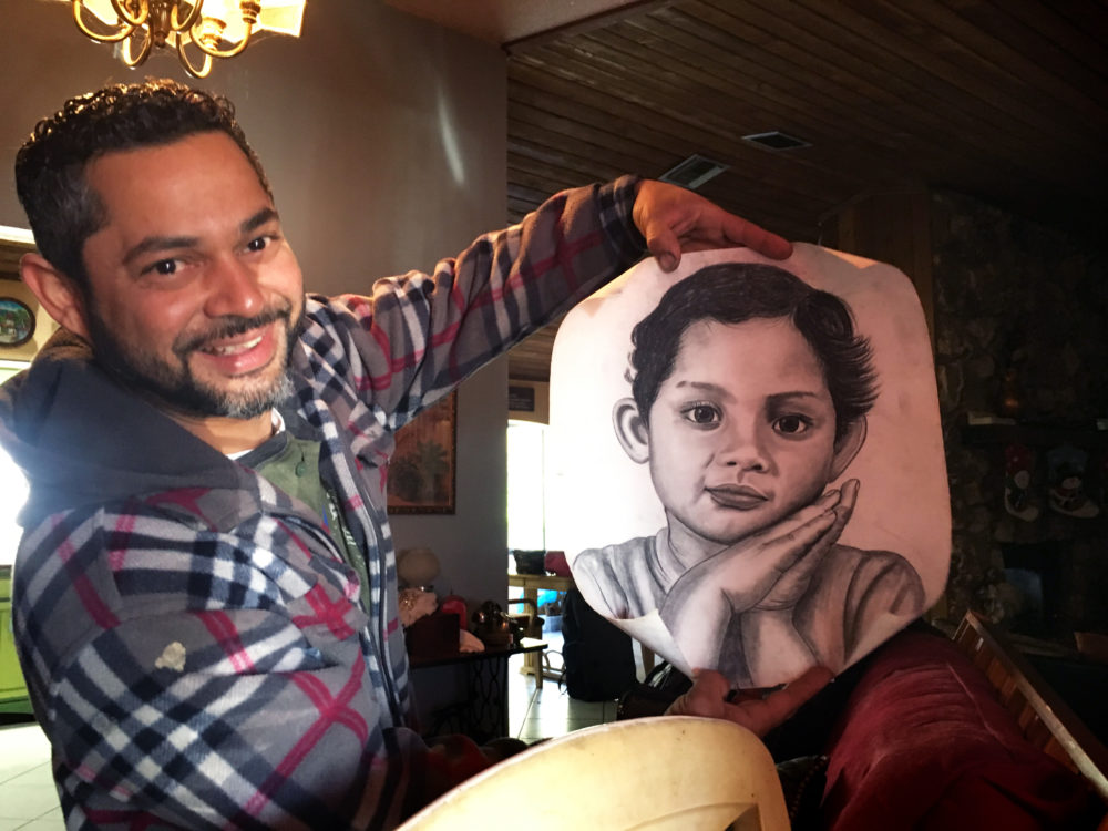 Roque Cartagena holds up a charcoal portrait he made of his daughter when she was a baby. (Kelly Horan/WBUR)