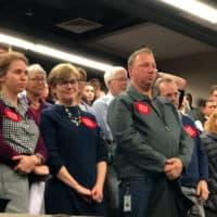 Newton community members stood in support of teachers at this week's meeting. (Max Larkin/WBUR)