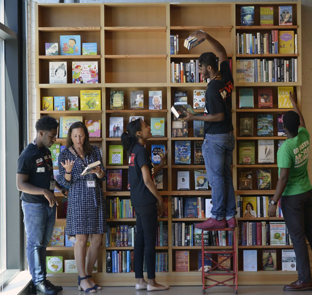 More Than Words Founder and CEO Jodi Rosenbaum, second from left, talks to employees at the newly expanded bookstore. (Courtesy of More Than Words)