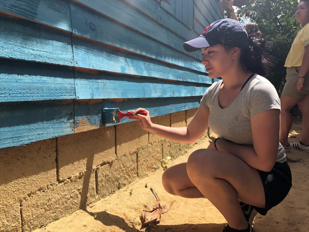 Maria Figueroa paints a home as part of a trip to the Dominican Republic. (Courtesy, Summer Search)