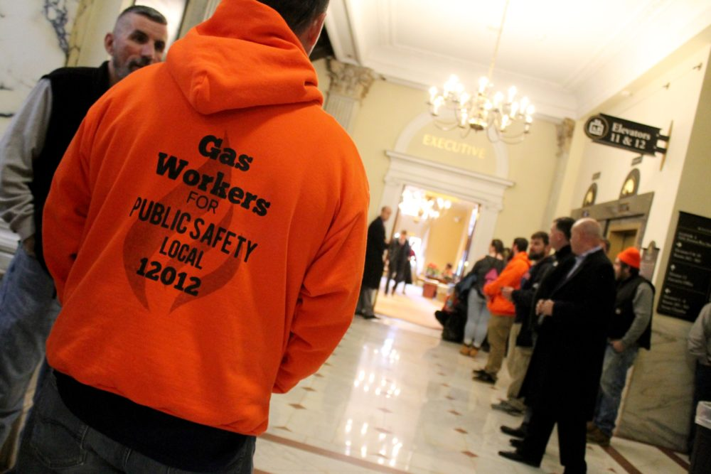 Locked out National Grid workers and their union presidents gathered in the hallway outside Gov. Charlie Baker's office after the Legislature sent Baker a bill to extend the gas workers' unemployment benefits. (Sam Doran/SHNS)