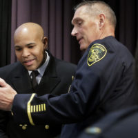 United States Surgeon General Jerome Adams, left, and Arlington, Mass., Police Chief Frederick Ryan, center, look at a mobile phone during a break at a national summit focused on police efforts to address the opioid epidemic on Thursday. (Steven Senne/AP)