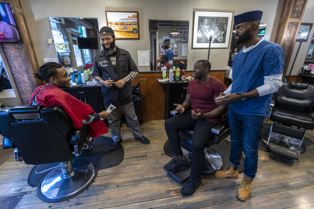 "From right to left: Bright Genty and his father, master barber Isaac, speak with ""Barber Shop Chronicles"" actor Ekow Quartey and the production's writer Inua Ellams at Headlines Unisex Barbershop in Cambridge. (Jesse Costa/WBUR)"