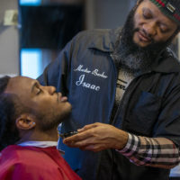 Master barber Isaac Genty trims the beard of his son Bright, who is training to become a barber himself at Headlines Unisex Barber Shop in Cambridge. (Jesse Costa/WBUR)
