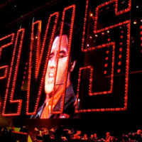 "The red ""Elvis"" sign from the 1968 Elvis ""comeback special"" is projected at the start of the Elvis Presley 25th Anniversary Concert in Memphis, Tenn., in 2002. (Stephan Savoia/AP)"