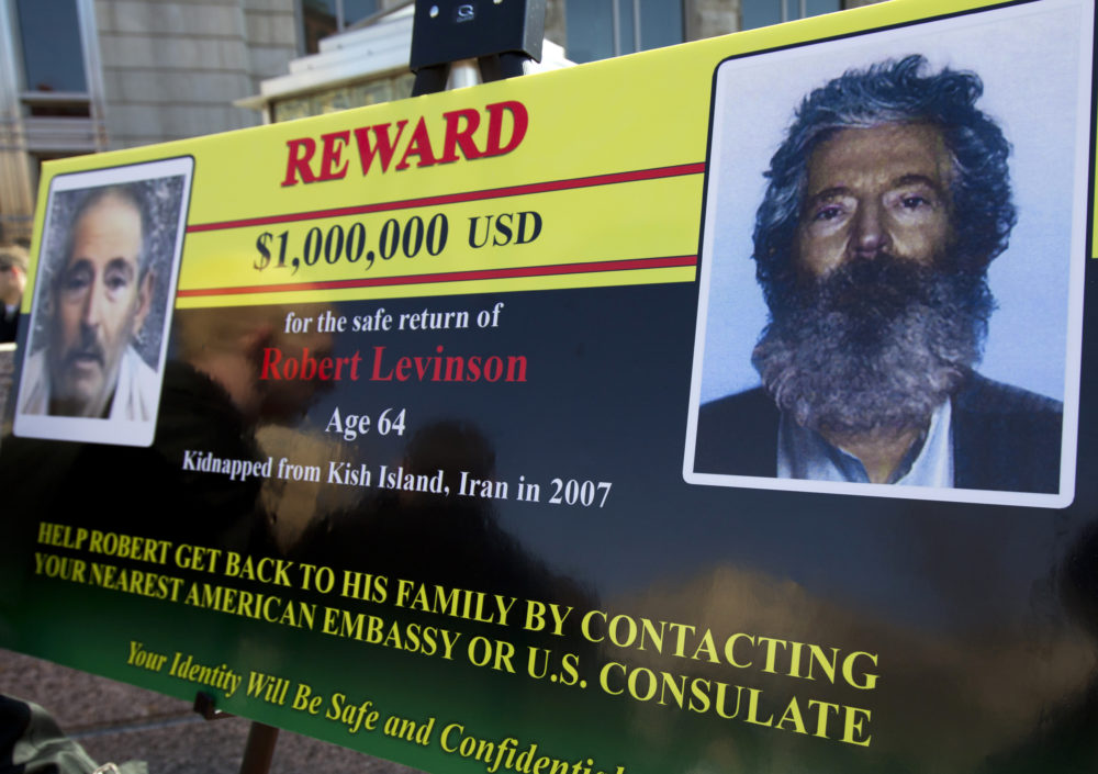 An FBI poster showing a composite image of former FBI agent Robert Levinson, right, of how he would look like after five years in captivity, and an image, left, taken from the video, released by his kidnappers, March 6, 2012, in Washington during a news conference. (Manuel Balce Ceneta/AP)