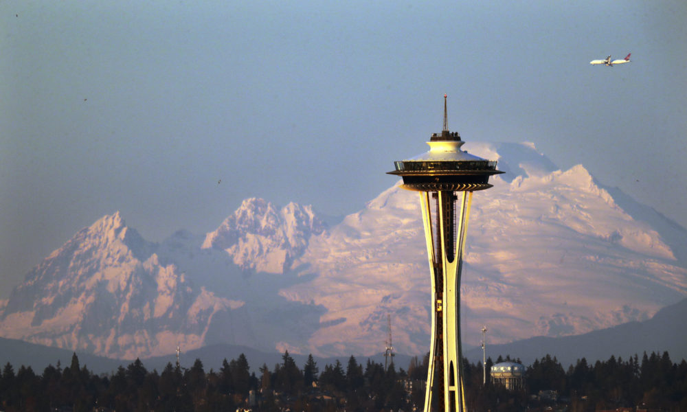 Mount Baker is seen some 85 miles distant behind the Space Needle under clear skies at sunset Thursday, Dec. 6, 2018, from Seattle. (Elaine Thompson/AP)