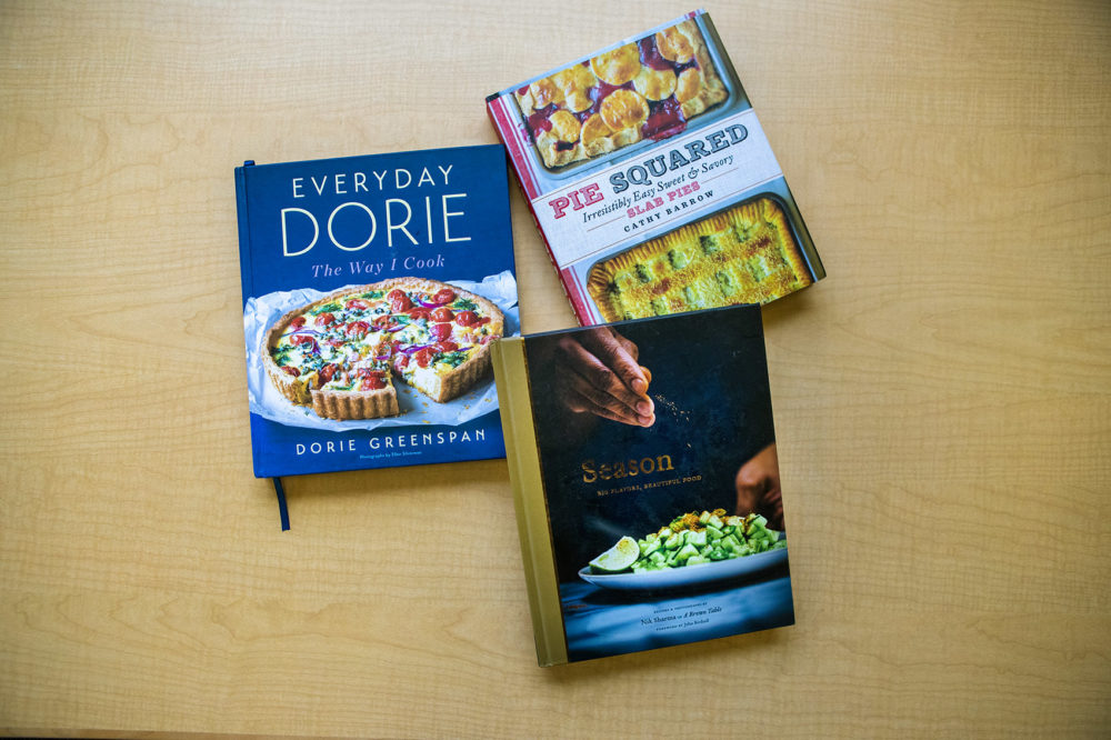 """Three of chef Kathy Gunst's favorite cookbooks of 2018: """"Pie Squared: Irresistibly Easy Sweet & Savory Slab Pies,"""" by Cathy Barrow; """"Everyday Dorie: The Way I Cook,"""" by Dorie Greenspan; """"Season: Big Flavors, Beautiful Food,"""" by Nik Sharma. (Jesse Costa/WBUR)"""