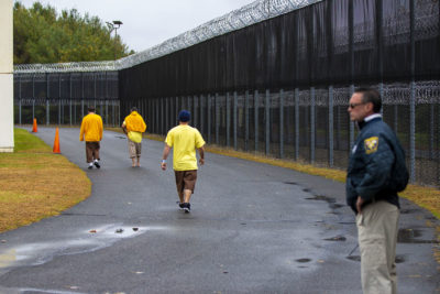 Men who have been civilly committed to the addiction treatment unit at the Hampden County Jail in Ludlow walk around a fenced-in path to get some exercise. (Jesse Costa/WBUR)