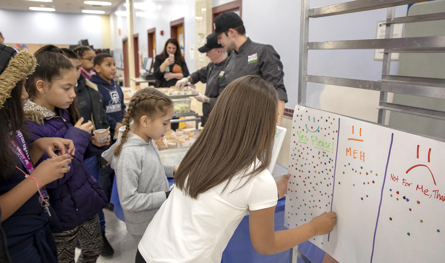 """Students at Parthum Elementary give feedback on the day's taste test. """"Yes please"""" means students loved it. """"Meh"""" and """"Not for me"""" mean Icklan needs to tweak the recipe. (Robin Lubbock/WBUR)"""