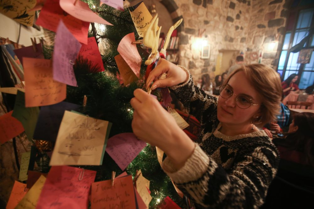 A Syrian youth hangs on a Christmas tree New Year wishes written on a card in a coffee shop in the Syrian capital Damascus on Dec. 17, 2017. (Youssef Karwashan/AFP/Getty Images)
