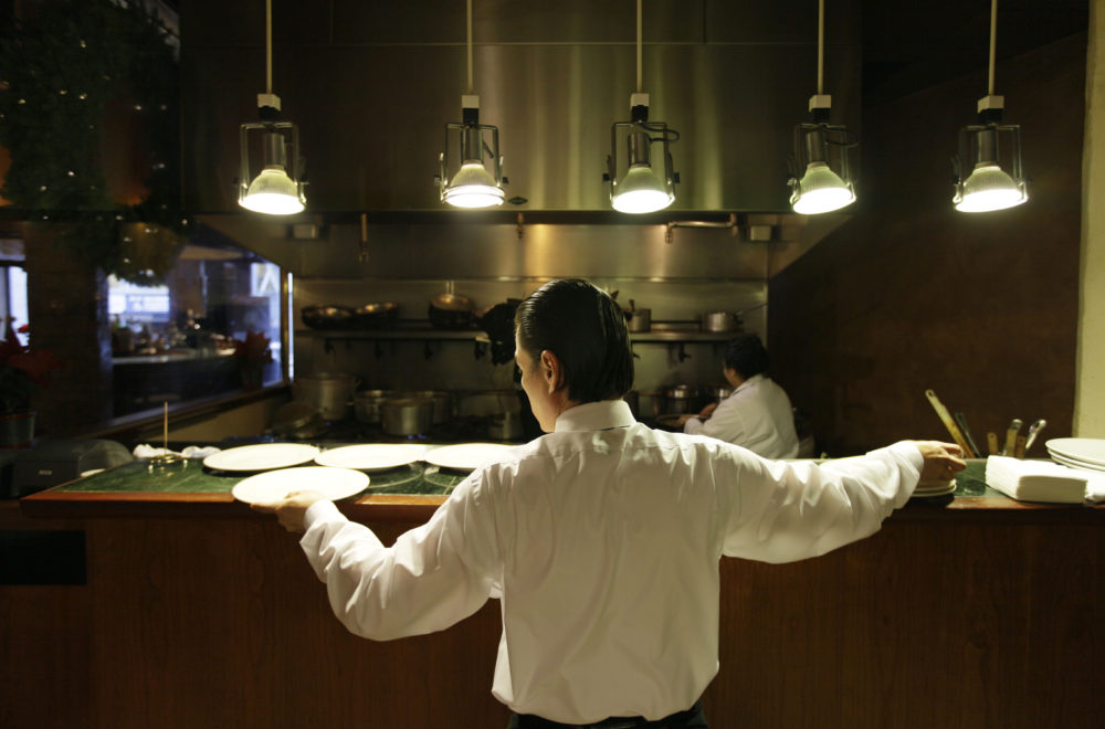 Nearly all restaurants in the U.S. operate under the tip system: Servers and those in the back of the house — chefs, line cooks, dishwashers, etc. — are paid a lower-than-average standard minimum wage, and then they earn tips to make up for the pay disparity. (Eric Risberg/AP)