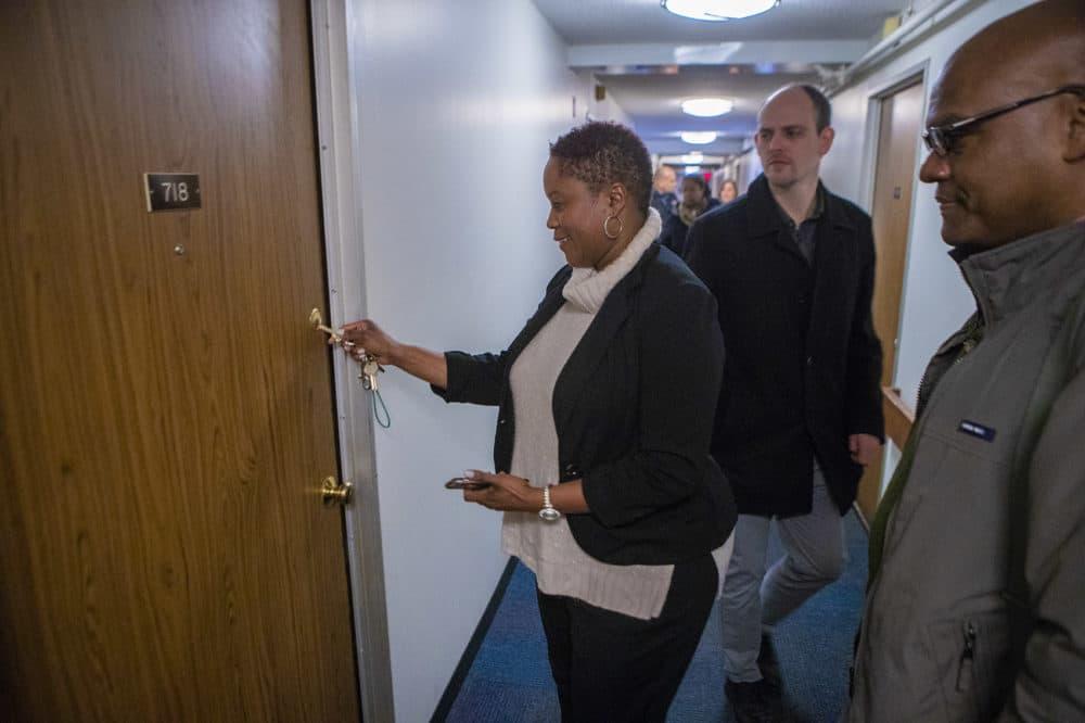 Property manager Monica Daniel puts the key into the door of Brian DeSilva's new studio apartment. (Jesse Costa/WBUR)
