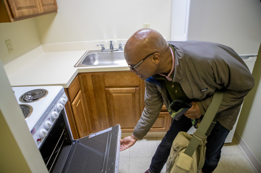 DeSilva checks out the oven in his new apartment. (Jesse Costa/WBUR)
