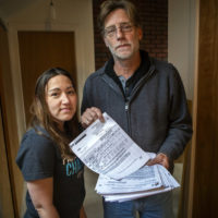 Kristina Cunningham is seen with her dad, Jim Royer, who holds her MedFlight bill totaling hundreds of thousands of dollars. (Jesse Costa/WBUR)