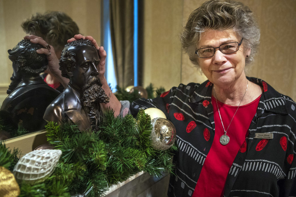 Historian Susan Wilson places her hand on a bust of Charles Dickens at the Omni Parker House, where he stayed in during his visit to Boston in 1867. (Jesse Costa/WBUR)