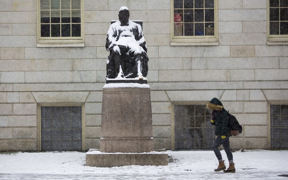 A student on her way to class passes a snow covered John Harvard in Harvard Yard on Monday, April 4, 2016. (Jesse Costa/WBUR)