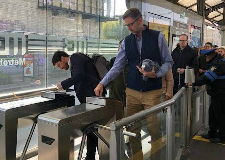 Will Foley of Cushman & Wakefield and Dave McLaughlin of WeWork scan their bus passes to enter the boarding area for a line of the Metrobus in Mexico City. (Courtesy Alliance for Business Leadership)