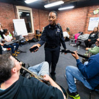 "Kerline Desire, a Boston police officer, talks with colleagues at a ""Code Listen"" rehearsal. Desir says her experience with Code Listen reminds her that there's ""a story behind each victim we encounter on the streets. (Courtesy Celebrity Series)"
