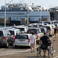 Passengers with cars and bicycles prepare to board a ferry departing the island of Martha's Vineyard, in Oak Bluffs on Aug. 26, 2011. (Steven Senne/AP)