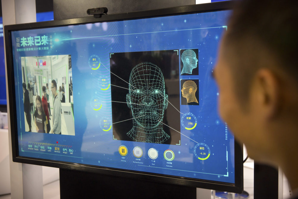 A man watches as a visitor tries out a facial recognition display at a booth for Chinese tech firm Ping'an Technology at the Global Mobile Internet Conference (GMIC) in Beijing on April 26, 2018. (Mark Schiefelbein/AP)