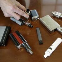 Marshfield High School Principal Robert Keuther displays vaping devices that were confiscated from students in such places as restrooms or hallways at the school in Marshfield, Mass. Health and education officials across the country are raising alarms over wide underage use of e-cigarettes and other vaping products. The devices heat liquid into an inhalable vapor that's sold in sugary flavors like mango and mint, and often with the addictive drug nicotine. (Steven Senne/AP)