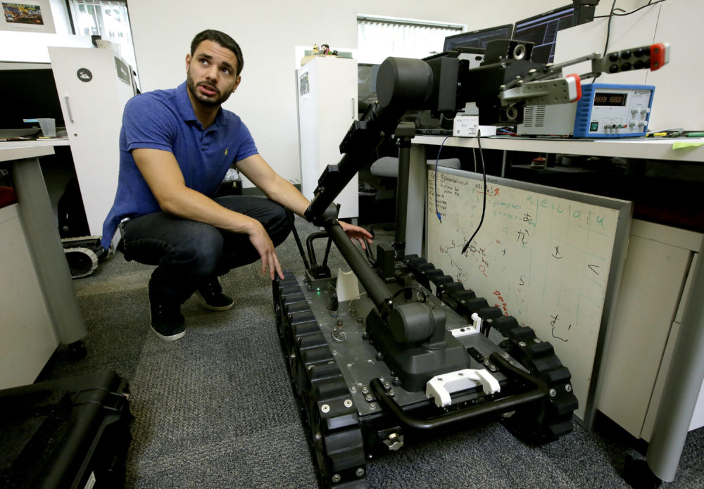 In this Aug. 28, 2018 photo, software engineer Nicholas Otero, of Woburn, Mass., speaks with a colleague about features on a Centaur robot, right, at Endeavor Robotics in Chelmsford, Mass.  The Army is looking for a few good robots. These robots won't fight, at least not yet. But they will be designed to help the men and women who do. The companies making them are waging a different kind of battle. At stake is a contract worth almost half a billion dollars for 3,000 backpack-sized robots that can defuse bombs and scout enemy positions. (Steven Senne/AP)