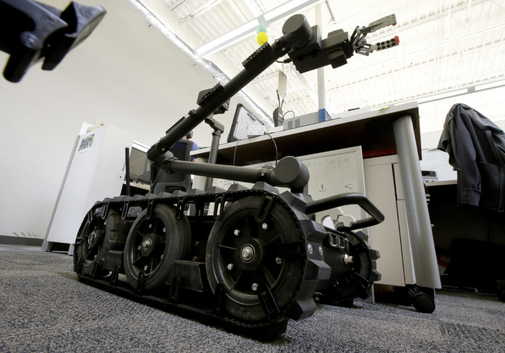 In this Aug. 28, 2018 photo a Centaur robot rests on a carpeted floor between desks at Endeavor Robotics in Chelmsford, Mass. The Army is looking for a few good robots. These robots won't fight, at least not yet. But they will be designed to help the men and women who do. The companies making them are waging a different kind of battle. At stake is a contract worth almost half a billion dollars for 3,000 backpack-sized robots that can defuse bombs and scout enemy positions. (Steven Senne/AP)