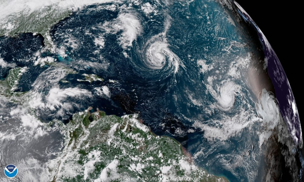 This enhanced satellite image made available by NOAA shows Tropical Storm Florence, center, in the Atlantic Ocean on Saturday, Sept. 8, 2018. (NOAA via AP)