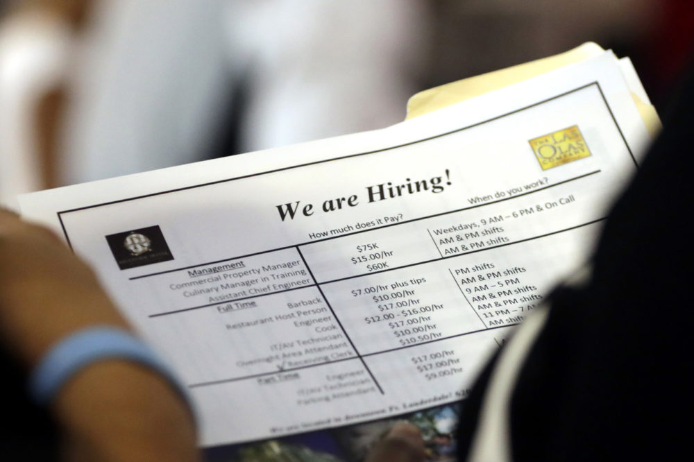 A job applicant looks at job listings for the Riverside Hotel at a job fair hosted by Job News South Florida, in Sunrise, Fla, June 21, 2018. (Lynne Sladky/AP)