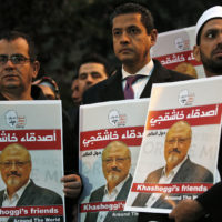 Activists protesting the killing of Saudi journalist Jamal Khashoggi hold a candlelight vigil outside Saudi Arabia's consulate in Istanbul, Thursday, Oct. 25, 2018. The posters read in Arabic:' Khashoggi's Friends Around the World'. (Lefteris Pitarakis/AP)