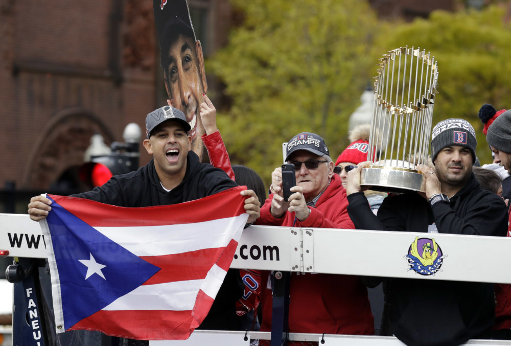 Boston Red Sox manager Alex Cora, left, waves the flag of Puerto Rico as coach Ramon Vazquez holds the championship trophy during a parade to celebrate the team's World Series championship over the Los Angeles Dodgers, Wednesday, Oct. 31, 2018, in Boston. (Elise Amendola/AP)