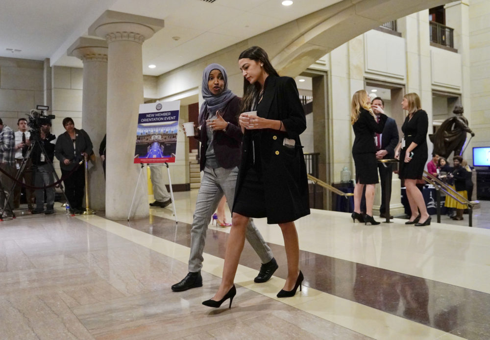 Rep.-elect Alexandria Ocasio-Cortez, D-N.Y., right, walks and talks with Rep.-elect IIhan Omar, D-Minn., left, prior to a member-elect briefing on Capitol Hill in Washington. (Pablo Martinez Monsivais/AP)