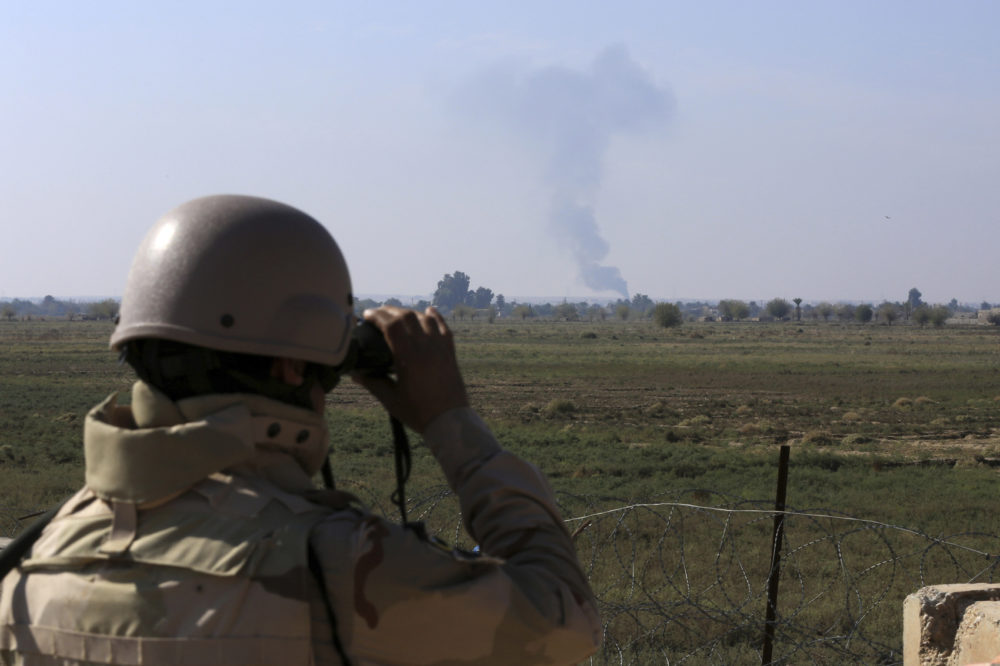 An Iraqi soldier watches smoke rising after an airstrike by U.S.-led international coalition warplanes against ISIS, on the border between Syria and Iraq in Qaim, Anbar province, Iraq, Nov. 13, 2018. (Hadi Mizban/AP)