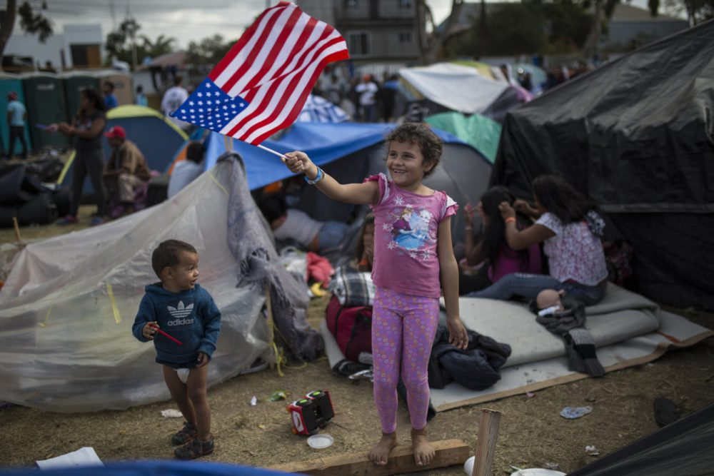 Seven-year-old Honduran migrant Genesis Belen Mejia Flores waves an American flag at U.S. border control helicopters flying overhead near the Benito Juarez Sports Center serving as a temporary shelter for Central American migrants, in Tijuana, Mexico, Saturday, Nov. 24, 2018. (Rodrigo Abd/AP)