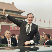 "Former U.S. President  George H.W. Bush stands on his car and waves to crowds in Tiananman Square in Beijing, Feb. 25, 1989. Chinese state media are praising Bush as a ""statesman of vision,"" recalling the late president's role in helping end the Cold War and establishing policies toward China. (Doug Mills, File/AP)"