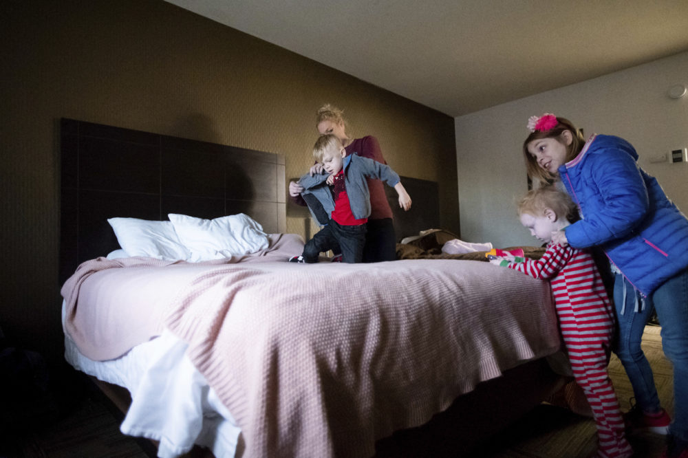Erica Hail, back left, dresses son Vance Maloney, 5, while preparing her children for their first day of school since the Camp Fire destroyed their home, Monday, Dec. 3, 2018, in Yuba City, Calif. Jaxon Maloney, 2, second from right, and Bella Maloney, 8, right, look on. The family, who lost their five-bedroom home in Paradise, plans to stay in a hotel room through February. (Noah Berger/AP)