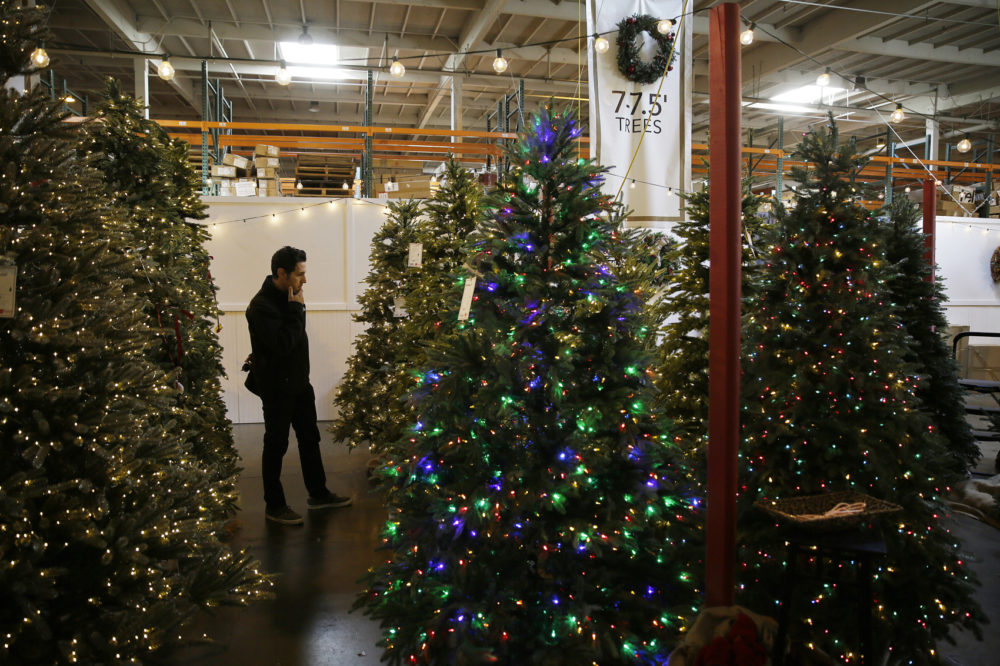 a man looks at artificial christmas trees for sale at the balsam hill outlet store in