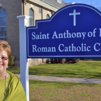 In this Dec. 7, 2018 photo provided by the Diocese of Bridgeport, Eleanor Sauers stands outside Saint Anthony of Padua Roman Catholic Church in Fairfield, Conn. Sauers, a lay woman, has been put in charge of the local parish months after the death of its priest. Her official title will be parish life coordinator and she takes the new position in January. Bishop Frank J. Caggiano has given her decision-making authority at the church, where a team of priests will say Mass and perform other ministerial duties. (Joe Pisani/Diocese of Bridgeport via AP)