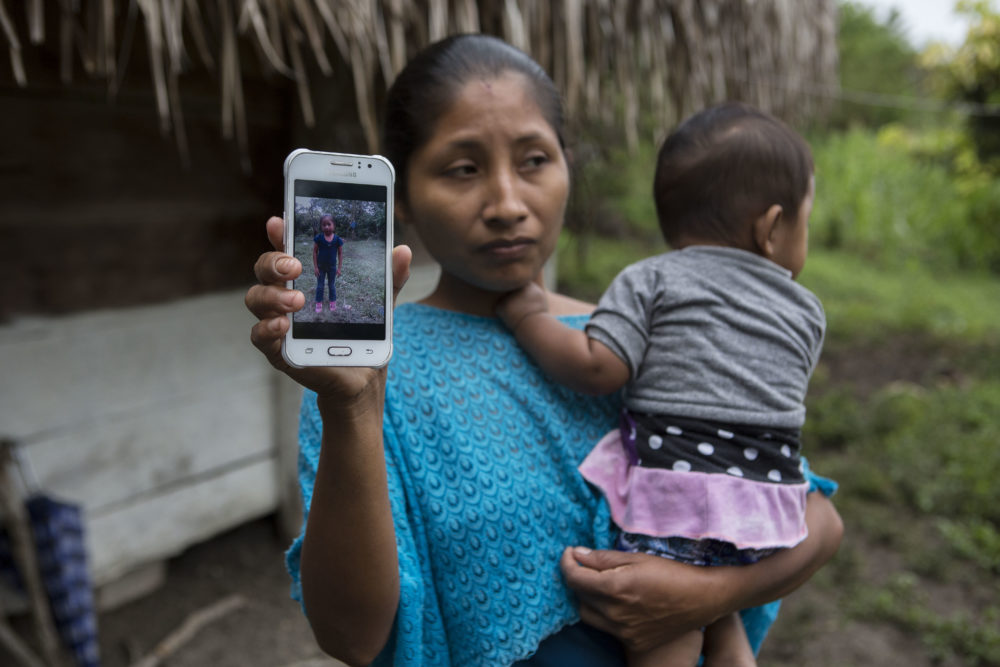 Claudia Maquin, 27, shows a photo of her daughter, Jakelin Amei Rosmery Caal Maquin in Raxruha, Guatemala, on Dec. 15, 2018. The 7-year-old girl died in a Texas hospital, two days after being taken into custody by border patrol agents in a remote stretch of New Mexico desert. (Oliver de Ros/AP)