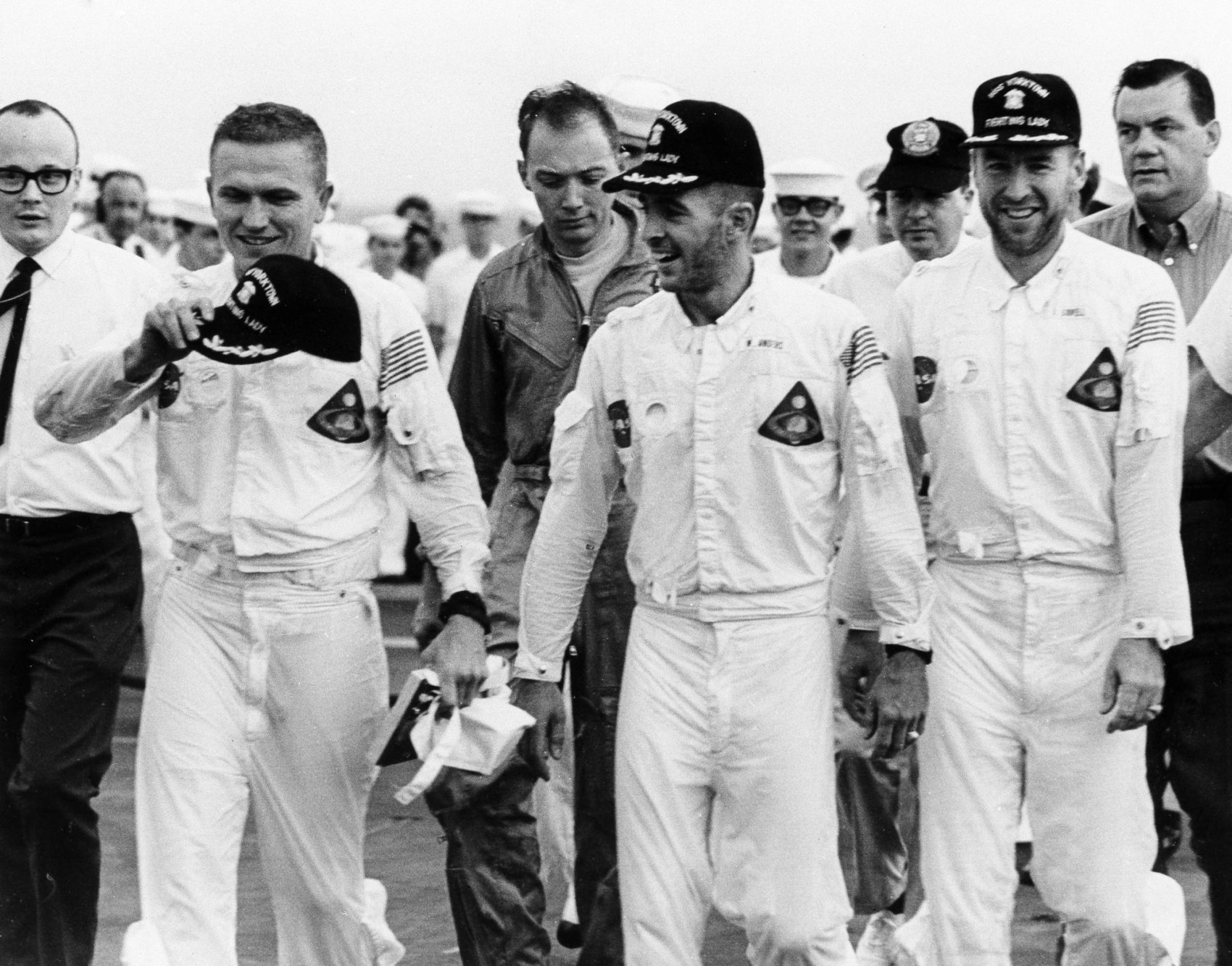 Three happy Apollo 8 astronauts Frank Borman left William A. Anders center and James A. Lovell stroll across the deck of the USS Yorktown after their recovery from the Pacific Ocean Dec. 28 1968