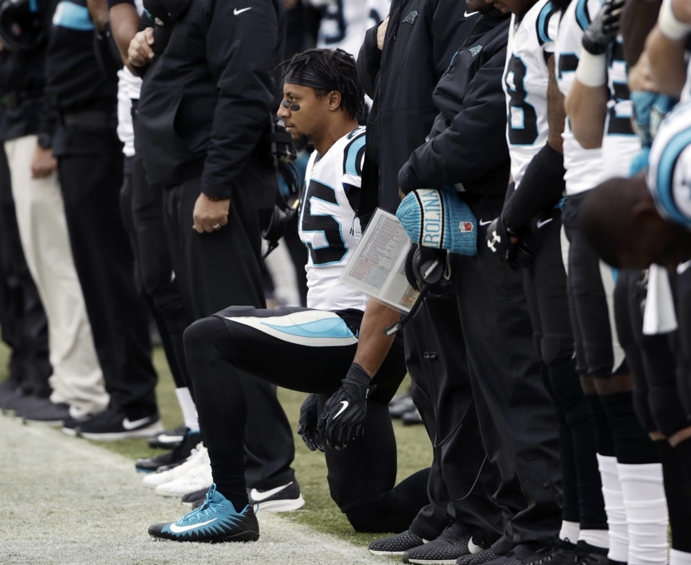 Carolina Panthers strong safety Eric Reid, center, takes a knee during the playing of the national anthem before an October game against the Philadelphia Eagles. (Matt Rourke/AP)