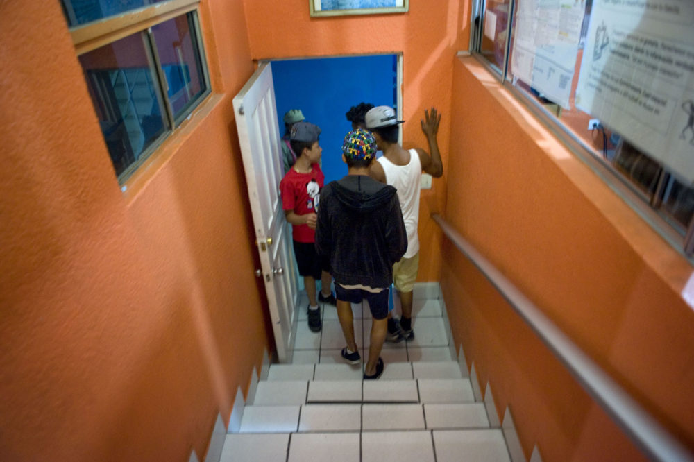 Vladimir, 15, center, walks down the stairs of a shelter for migrant minors in Tijuana, Mexico. Vladimir traveled on a migrant caravan across Mexico with his grandmother. (David Maung/KQED)