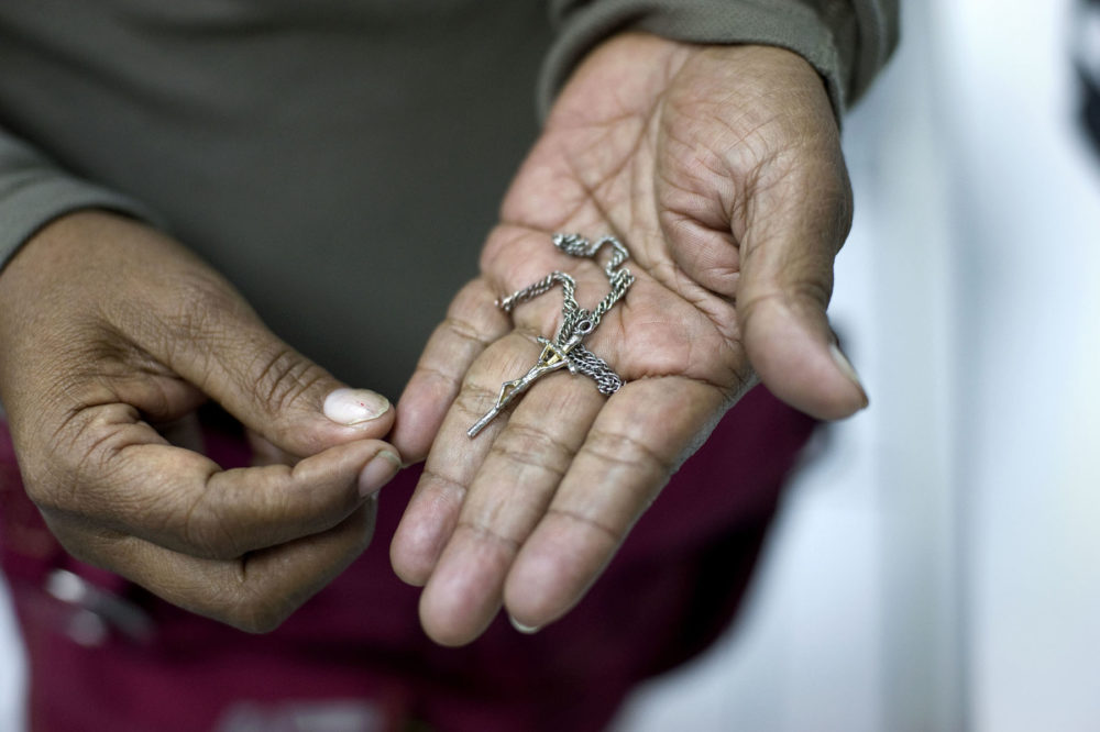 Luci Diaz holds a crucifix her 15-year old grandson gave her before they separated in Tijuana on Nov. 20, 2018. Diaz accompanied her grandson in a migrant caravan so that he can ask U.S. officials for asylum and join his mother in the Bay Area. (David Maung/KQED)
