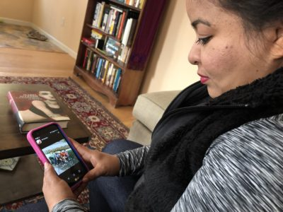 Veronica Aguilar looks at a photo of her family in El Salvador in the Moriartys' living room in Pinole on Nov. 18, 2018. Aguilar, an asylum applicant, traveled to the U.S. border in a caravan last year. (Farida Jhabvala Romero/KQED)
